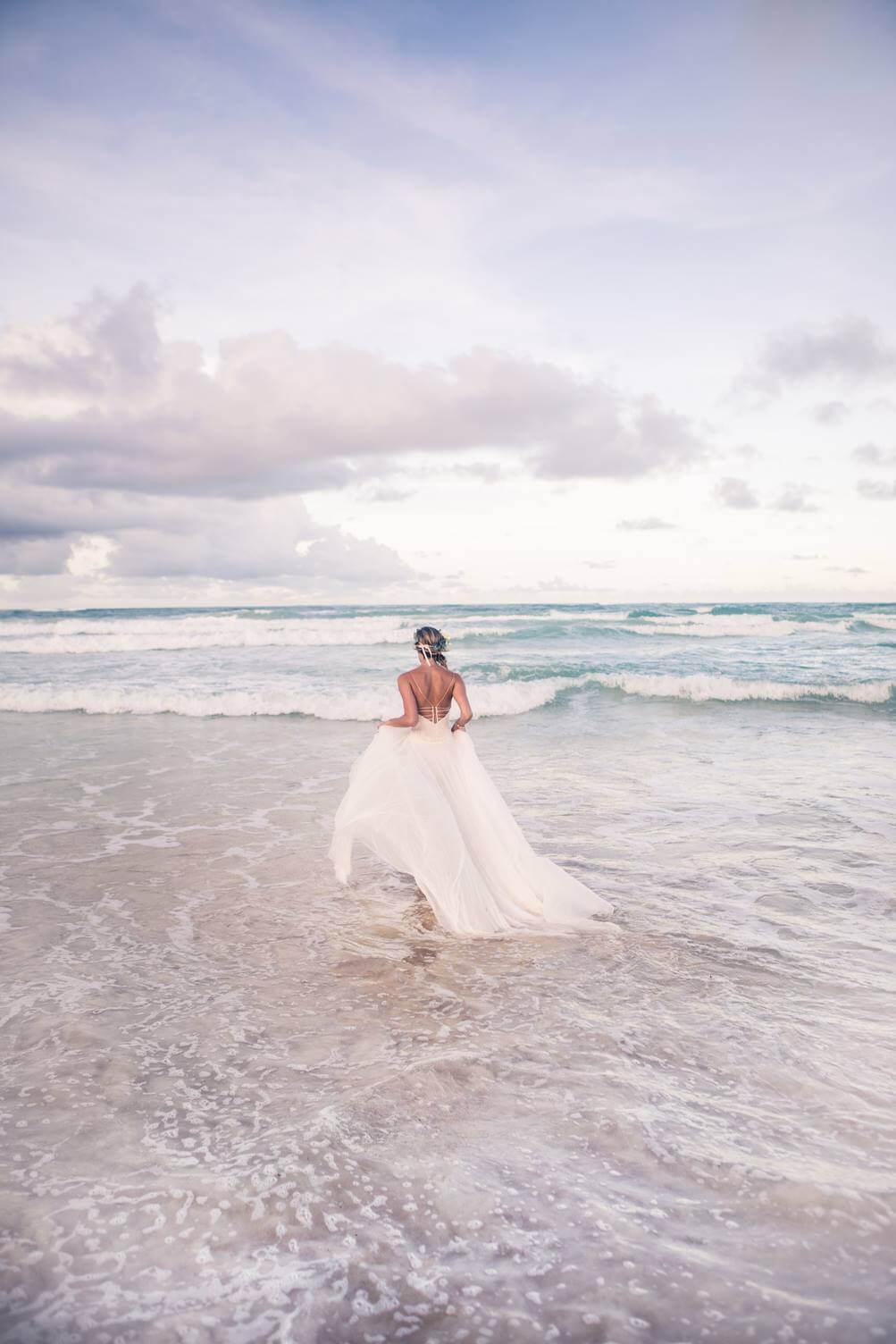 Cancun wedding bride walking into ocean